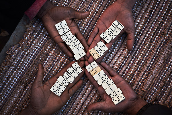 A group of refugees plays domino in The Jungle (Calais, France), in March of 2016.