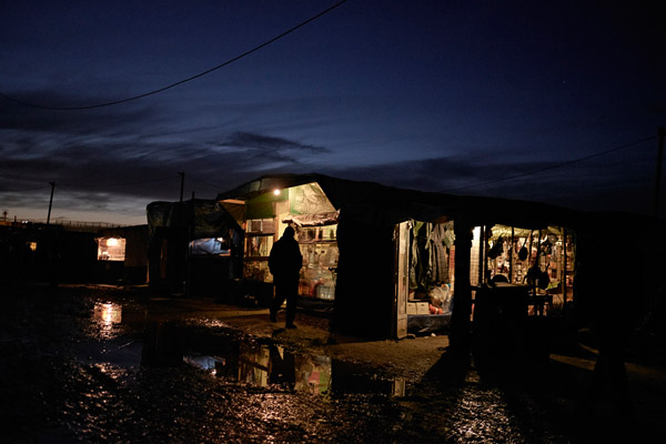 A man walks right next to a shop at night in The Jungle (Calais, France), in March of 2016. Most of the shops in the refugee camp of Calais belongs to the mafia.