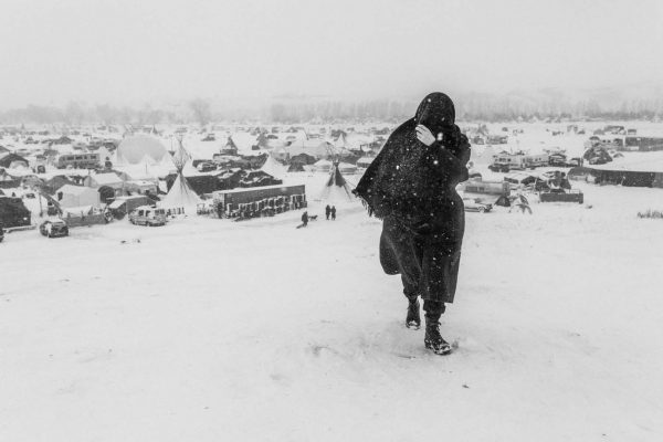 A woman walks in the snow during a blizzard. Cannon Ball, North Dakota, USA. November, 2016.