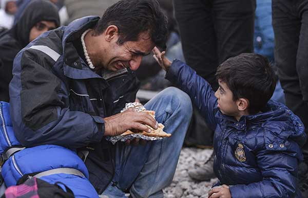 epaselect epa05033142 A small boy touches his crying father during a protest by migrants from Pakistan and Morocco who block the border line between Greece and Macedonia after Macedonia has started granting passage only to refugees from Syria, Iraq and Afghanistan, near Gevegelija, The Former Yugoslav Republic of Macedonia, 19 November 2015. Macedonia, Serbia and Croatia have started restricting access to migrants on the Balkan route to Syrians, Iraqis and Afghans. It is a part of a joint effort to reduce the number of asylum seekers streaming into the European Union.  EPA/GEORGI LICOVSKI